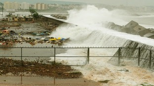 Waves crash onto the shore at a fishing harbour in Visakhapatnam district.