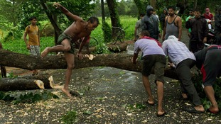 Men try to remove fallen trees from a road in the Indian state of Odisha.
