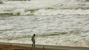 A man walks as waves from the Bay of Bengal approach the shore.
