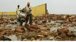 People walk among debris from a broken wall after it was damaged by a wave brought by Cyclone Phailin.
