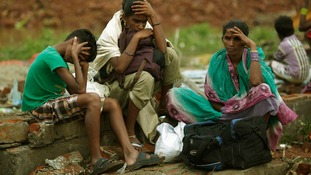 A family waits to board a boat as they return to their villages after Cyclone Phailin hit.