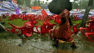 A woman walks past a fallen marquee and chairs set up for a Christian prayer service in Ranchi, India.