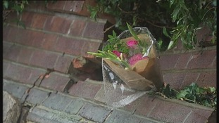 A mourner leaves a bunch of flowers at the scene of the crash