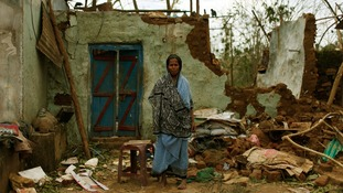 A woman stands outside her damaged house after Cyclone Phailin hit Gopalpur in eastern India.