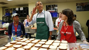 President Barack Obama tries to hear a question from a reporter as he helps the volunteers.