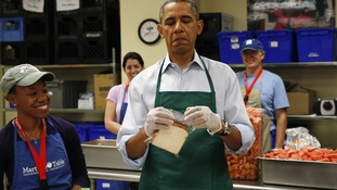 President Barack Obama has trouble closing a plastic bag at Martha's Table, a kitchen that provides meals for the homeless.