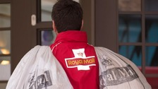 A postman with two bags of post.