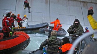 Russian coast guards wearing balaklavas intervene in a Greenpeace protest near an oil rig in the Arctic