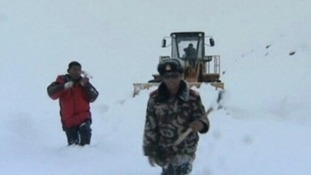 Rescue workers attempt to dig snow off the barely distinguishable road and mountain, on Monday afternoon.