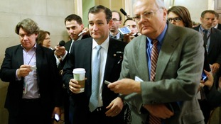 US Senator Ted Cruz (C) is trailed by reporters as he arrives at the Capitol