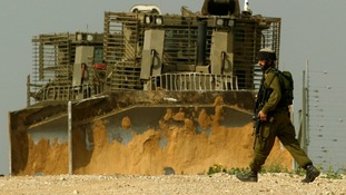 An Israeli soldier walks past military bulldozers near Kibbutz Kissufim, just outside Gaza