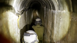 Israeli soldiers stand guard inside a tunnel exposed by the Israeli military