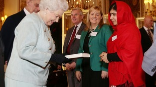 Malala presents the Queen with a copy of her book.