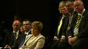 Deputy leader Nicola Sturgeon watches as party leader Alex Salmond delivers his address