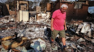 A homeowner surveys the wreckage left by wildfires that swept through the Blue Mountains suburb of Winmalee, west of Sydney.