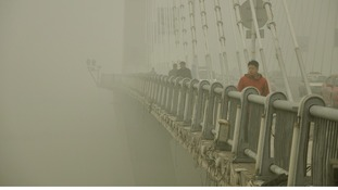 People walk on a bridge during a smoggy day in Jilin, Jilin province