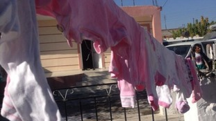 Children's clothes hang on the washing line outside the home.