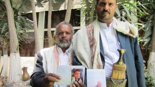 Hussain Jamil al-Qawli holds a picture of his 20-year-old son killed, and Muhammad al-Qawli holds a picture of his brother Ali.