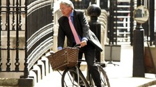 Andrew Mitchell riding on a bike at Downing Street.