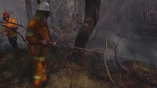 A firefighter hoses down a fire.