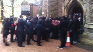 Mourners file into the church