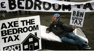 Protester with bedroom tax placard