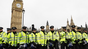 Police officers form a line in front of the Houses of Parliament as student protesters gathered nearby in central London November 30, 2010
