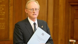 Tom Winsor with a copy of his review into police pay and conditions