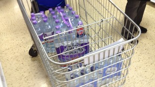 One customer fills their trolley with bottled water