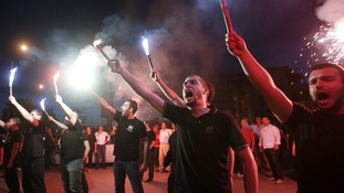 Supporters of the extreme-right Golden Dawn party raise flares as they celebrate polls results in Thessaloniki