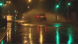 Cars drive through a flooded road in Plymouth.