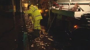Highway maintenance men try to clear drains in Plymouth to stop the flooding.