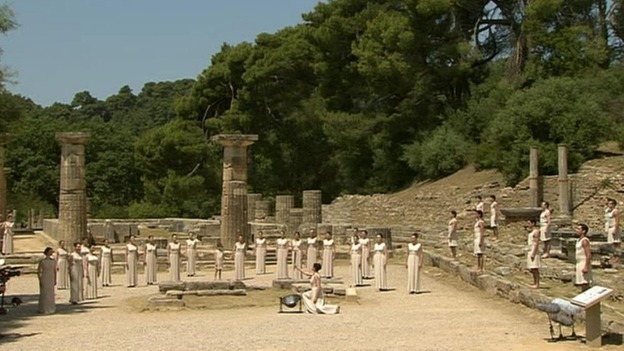 The flame is lit in front of the ancient ruins of the Temple of Hera