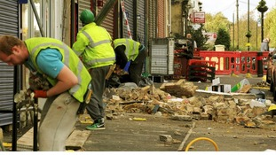Workers clean up damaged brick work in Leyton, east London