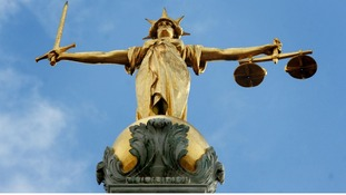 The gold statue of the figure of justice, holding scales and a sword, on top of the Old Bailey in London.