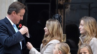 David Cameron poses with The Poppy Girls outside 10 Downing Street, ahead of the Royal British Legion's 2013 Poppy Appeal.
