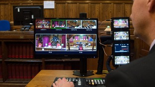 A man checks the monitors in Court Four at the Royal Courts of Justice in London.