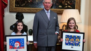 Prince Charles presents Molly Robson (left), aged seven, and Rosie Hargreaves, aged 10, with framed copies of their designs.