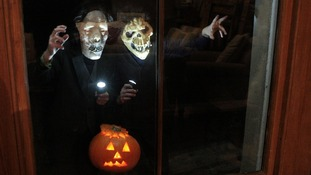 Children in Halloween costumes knock on windows.