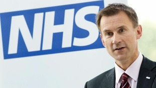 Health Secretary Jeremy Hunt with an NHS sign behind him.
