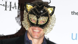 Easy option?: Hugh Grant sports an ornate cat mask at he UNICEF Halloween Ball at One Mayfair in London.
