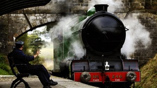 A steam train pulls up to station