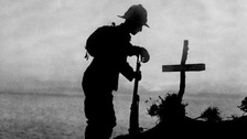 A British soldier pays his respects at the grave of a colleague in 1915.