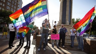 Dale Robinson waves his flag for people driving by a rally of the Dallas LGBT Community to applaud President Obama's stance on Gay marriage