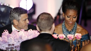 George Clooney sits beside Michelle Obama during the State Dinner for David Cameron in Washington in March.