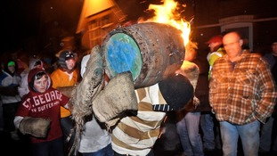 A boy carries the traditional Tar Barrel through the streets.