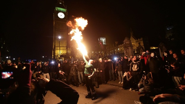 A woman breathes fire during the protests outside Westminster.