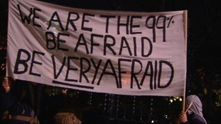 Protesters hold up a banner outside Trafalgar Square