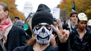 A supporter of the Anonymous movement gestures as she marches with a crowd of protesters with the US Capitol in the background.