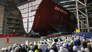 Workers watch as the forward section of aircraft carrier HMS Queen Elizabeth as it is moved on to barge on Portsmouth in May 2012.